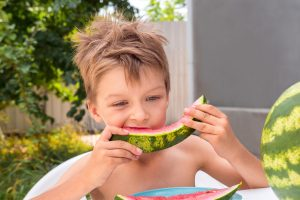 Boy with messy hair eating watermelon